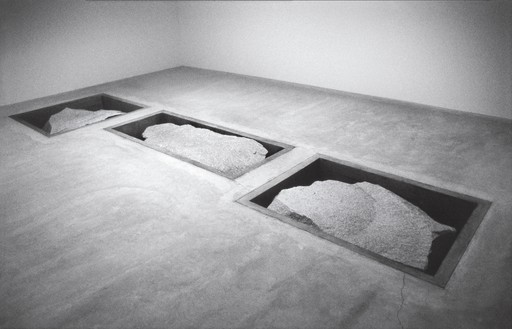 Michael Heizer, Displaced/Replaced Mass (3), 1994 20-ton white granite boulder and 2 15-ton white granite boulders in concrete pits, in 3 parts, part a: 17 feet × 6 feet 6 inches × 8 feet (5.2 × 2 × 2.4 m), parts b and c, each: 10 feet × 12 feet × 3 feet (3.1 × 3.7 × .9 m), installed at Ace Gallery, New York, July 1–August 15, 1994, Inhotim Collection, Brazil© Michael Heizer