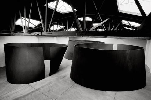 Installation view, Richard Serra: Torqued Ellipses, Dia Center for the Arts, New York, 1997–98. Left: Torqued Ellipse I (1996), right: Torqued Ellipse II (1996), back: Torqued Ellipse (1997) Artwork © 2018 Richard Serra/Artists Rights Society (ARS), New York. Photo: Dirk Reinartz