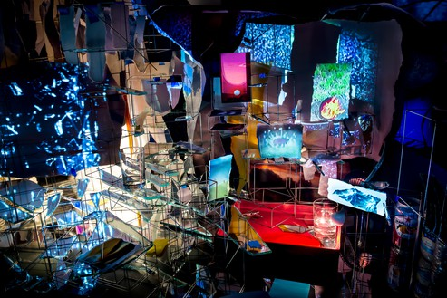 Sarah Sze, Timekeeper, 2016 (detail) Mixed media, including mirrors, wood, stainless steel, archival pigment prints, video projectors, lamps, desks, stools, and stone, overall dimensions variableInstallation view, Rose Art Museum, Brandeis University, Waltham, Massachusetts, 2016© Sarah Sze