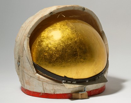 Tom Sachs, Gold Helmet, 2011 Duct tape, foam core, thermal adhesive, gold leaf, steel, plexiglass, synthetic polymer paint, and plywood, 12 ½ × 13 × 13 ½ inches (31.8 × 33 × 34.3 cm)© Tom Sachs. Photo: Genevieve Hanson