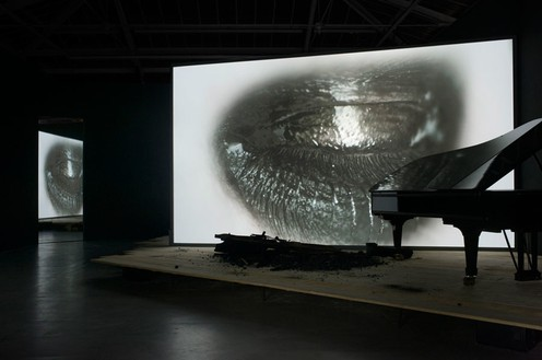 Douglas Gordon, Phantom, 2011 Video installation: a stage, a screen, a burnt Steinway piano, a black Steinway piano, and a monitor, dimensions variable, edition of 3© lost but found. Photo: Katharina Kiebacher