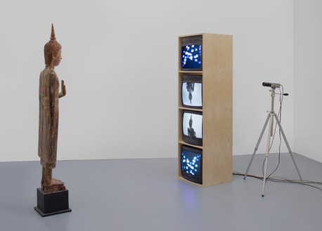 Nam June Paik, Standing Buddha with Outstretched Hand, 2005 Single-channel video (color, silent) with televisions, closed-circuit video (color), and wood Buddha with permanent oil marker, overall dimensions variable© Nam June Paik Estate