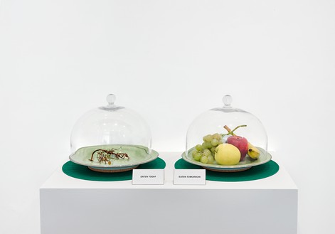 Davide Balula, Eaten today, Eaten tomorrow, 2017 Fruit, 2 ceramic plates, 2 glass bells, and furniture, 36 ½ × 31 ½ × 17 ⅝ inches (92.6 × 80 × 44.9 cm), edition of 3 + 2 AP© Davide Balula. Photo: Matteo D'Eletto