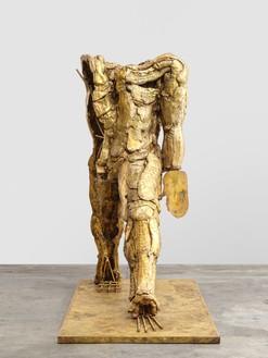 Thomas Houseago, Gold Walking Man, 2021 Bronze, 77 × 40 ⅞ × 84 ⅝ inches (195.6 × 104 × 215 cm), edition 1/3 + 2 AP© Thomas Houseago. Photo: Stefan Altenburger