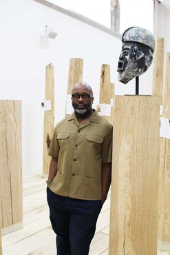 Theaster Gates with his work So Bitter, This Curse of Darkness (2019) in the exhibition Theaster Gates: Amalgam at the Palais de Tokyo, Paris, 2019. Artwork © Theaster Gates. Photo: © Palais de Tokyo, Paris