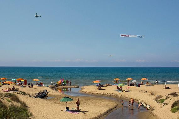 Lawrence Weiner's aerial banner Spaccato — Split (2020) in flight along the Italian coast. Artwork © Lawrence Weiner. Photo: Claudia de Nicolò