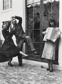 Black-and-white photograph of Alexander Calder and Margaret French dancing on a cobblestone street while Louisa Calder plays the accordion in front of a large window outside of James Thrall Soby's house, Farmington, Connecticut, 1936
