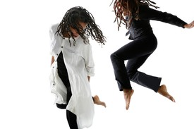 Bebe Miller and Cynthia Oliver in motion dancing, mid-jump, against a white background