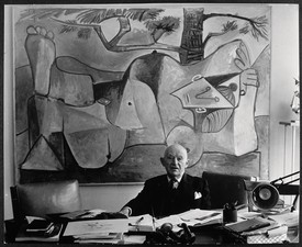 A black-and-white portrait of Daniel-Henry Kahnweiler seated at a desk in front of a painting by Pablo Picasso.