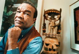 Dr. David Driskell, 2002, head resting on hand in a blue shirt with art in the background.