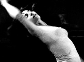 Black-and-white photograph of Aileen Passloff dancing in 1964. She is arched in a backbend, arm over her head