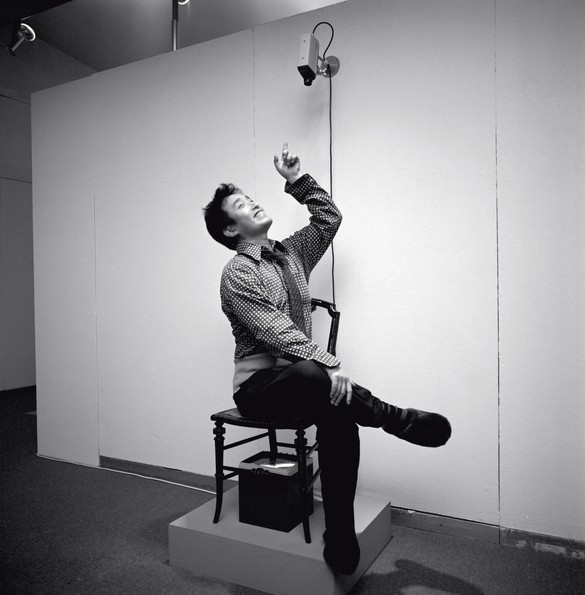 Nam June Paik sitting on TV Chair (1968/1976) in Nam June Paik Werke 1946–1976: Musik—Fluxus—Video, Kölnischer Kunstverein, Cologne, 1976. Photo: F. Rosenstiel, Cologne, Zentralarchiv des internationalen Kunsthandels (ZADIK), Cologne