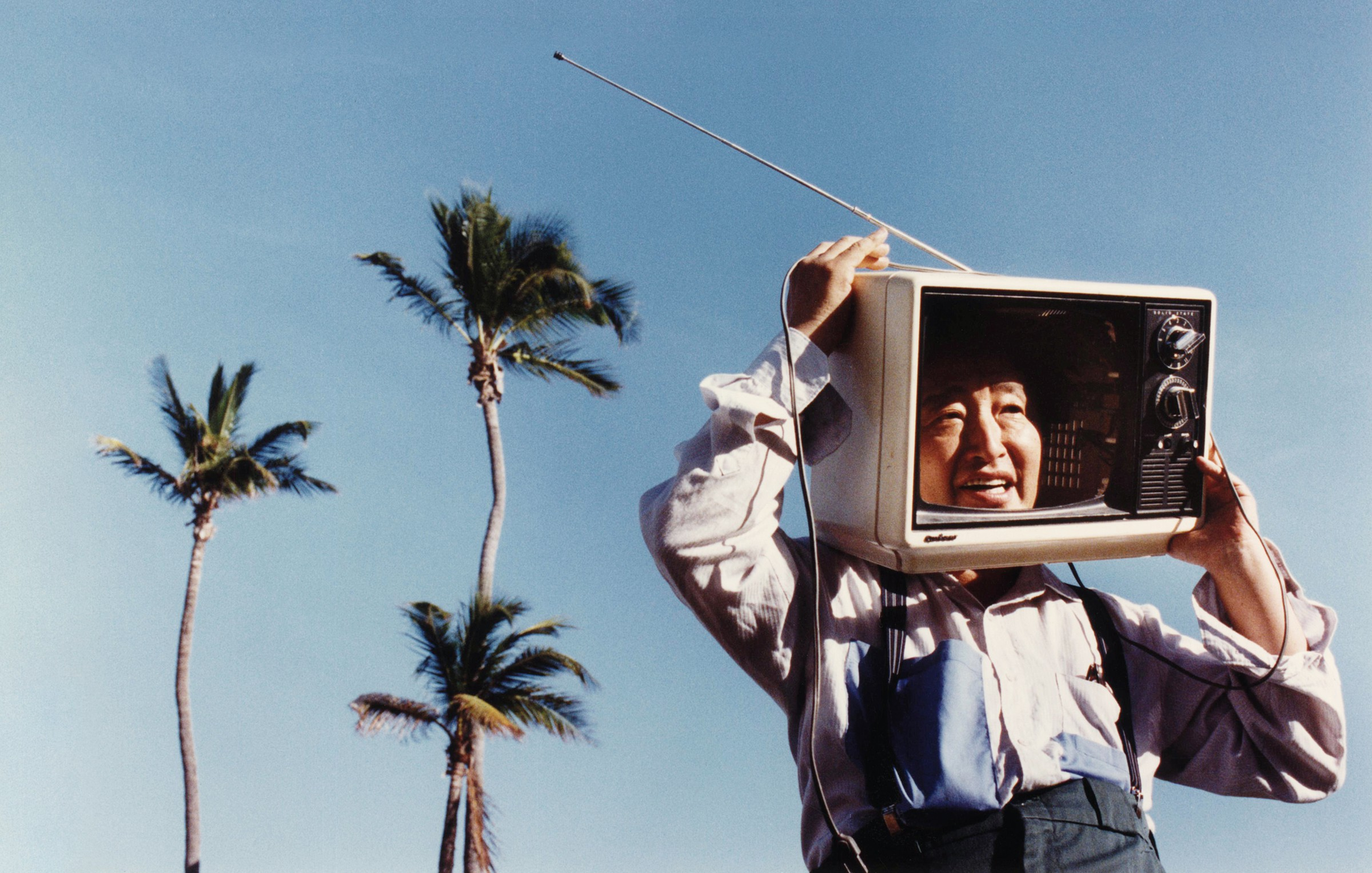 The artist Nam June Paik is shown with his head inside of an evacuated CRT television; behind Paik, three palm trees stand on a blue sky.