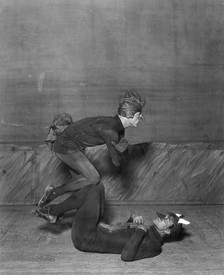 "Black and white image of two dancers, dressed as animals, balancing on each other's knees in the ballet ""Renard""."