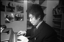 Artist Nam June Paik writing on his typewriter in black and white photo.