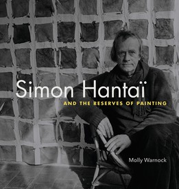 "Cover of ""Simon Hantaï and the Reserves of Painting"" by Molly Warnock. Simon Hantaï in front of a painting. Black and white photograph."