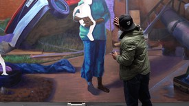 Titus Kaphar in his studio, touching his painting.