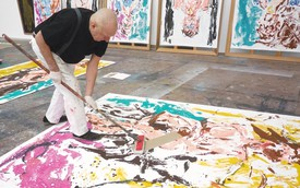 Georg Baselitz working on a painting in his studio.