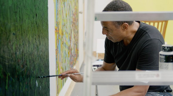 Rick Lowe painting in his studio.